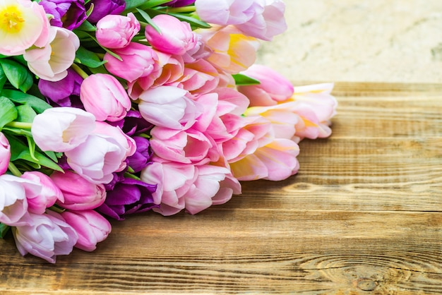 Close up of bunch of colorful tulips on wooden background Premium Photo