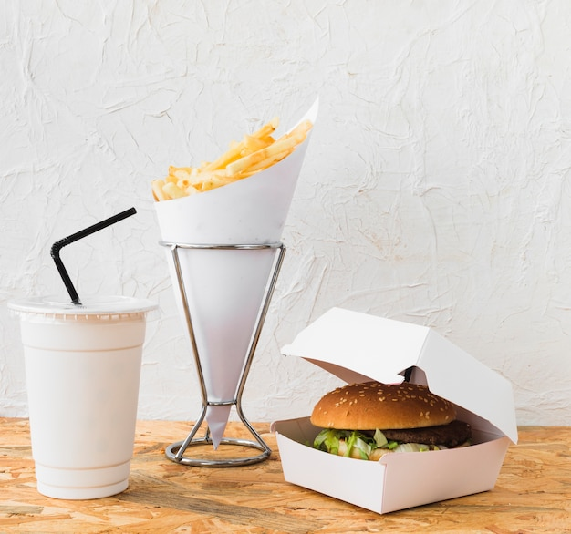 Close-up of burger; french fries and disposal cup on wooden desk Free Photo