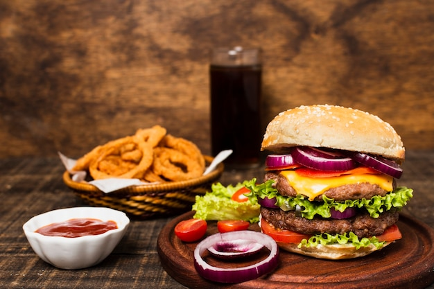 Close-up of burger with soda and onion rings Free Photo