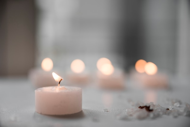 Close-up of burning candle and sea salt Free Photo