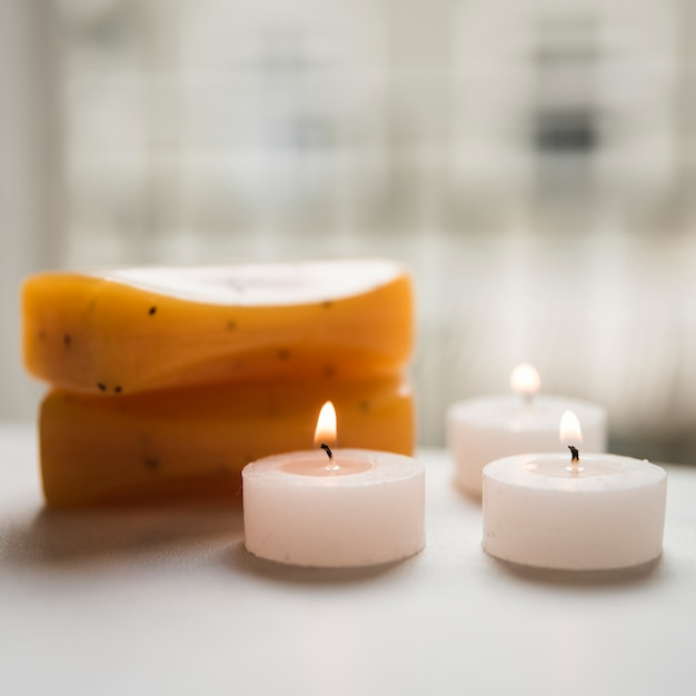 Close-up of burning candles and soaps in spa Free Photo
