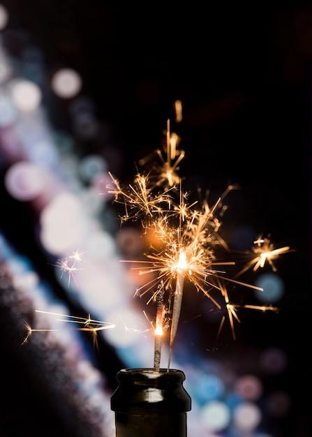 Primo piano della stella filante bruciante in bottiglia sul fondo del bokeh Foto Gratuite