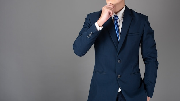 Close up of business man in blue suit is thinking on gray background Premium Photo