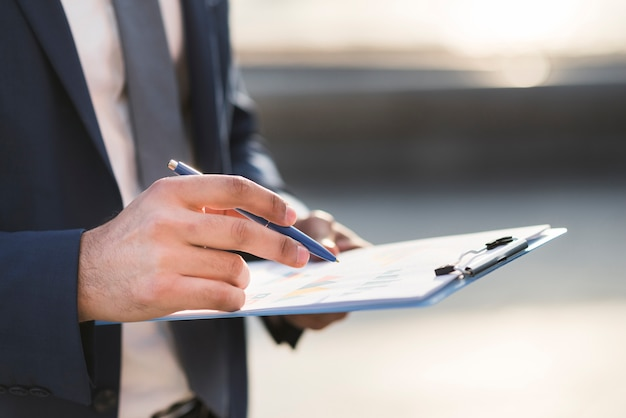 Close-up business man checking clipboard Free Photo