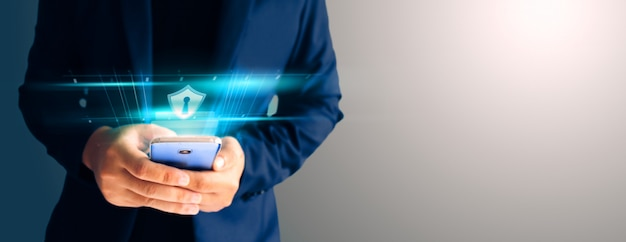 Close up business man formal blue suit use hold smart phone in the dark and copy space. use finger print unlock smart phone security. Premium Photo