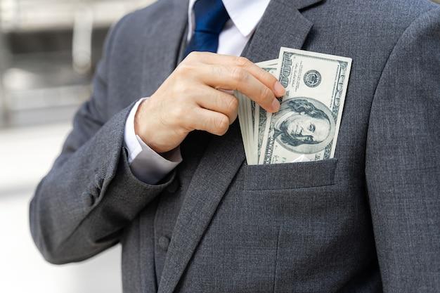 Close up business man holding money us dollar bills in hand Free Photo