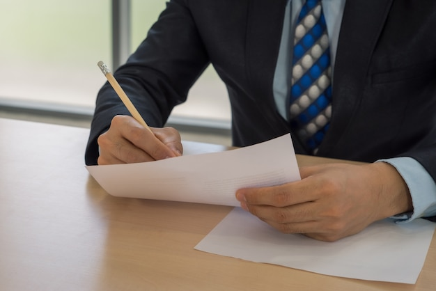 Close up business man writing or signing contract on paper in office. Premium Photo