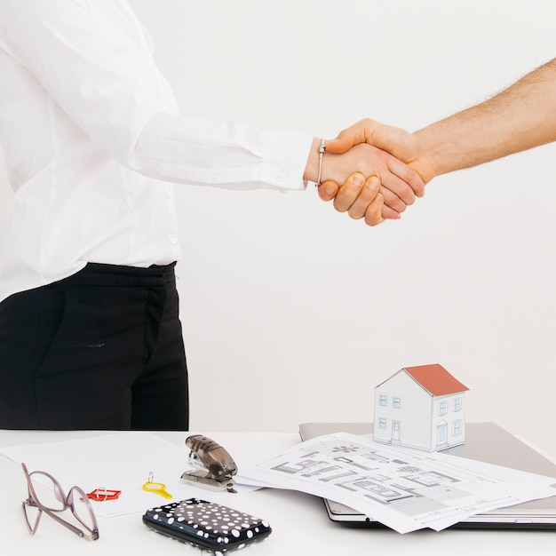 Close-up of business partners shaking hands after deal Free Photo