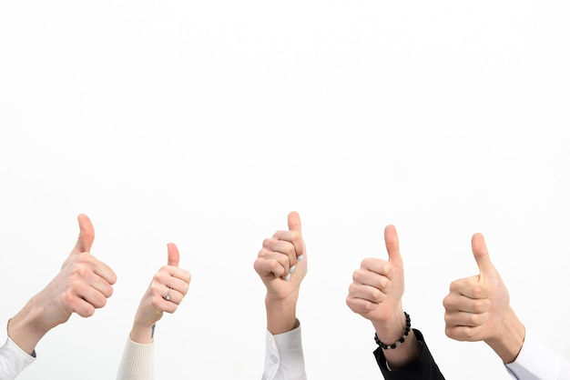Close-up of business people hand's showing thumb up sign isolated over white background Premium Photo