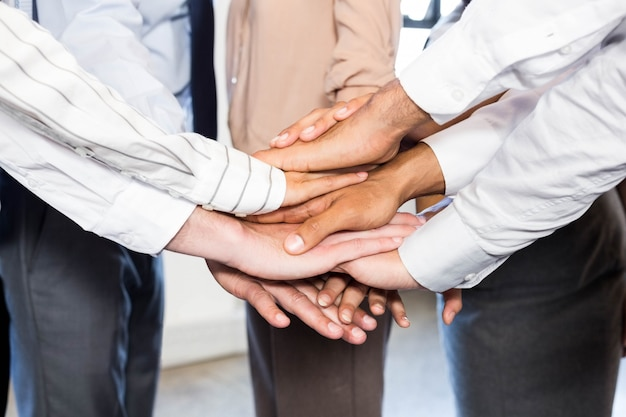 Close-up of business people stacking hands in office Premium Photo