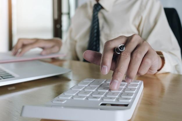 Крупным планом деловая женщина, использующая калькулятор и ноутбук для математических финансов на деревянном столе в офисе и бизнес, рабочий фон, статистика налогового учета и концепция аналитического исследования Premium Фотографии