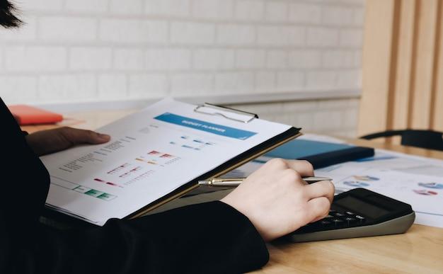 Крупным планом деловая женщина, использующая калькулятор и ноутбук для математических финансов на деревянном столе в офисе и бизнес-работе, налоговой, бухгалтерской, статистической и аналитической концепции исследования Premium Фотографии