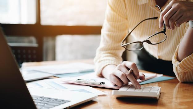 Закройте вверх по бизнес-леди используя калькулятор и компьтер-книжку для финансов математики на деревянном столе Premium Фотографии