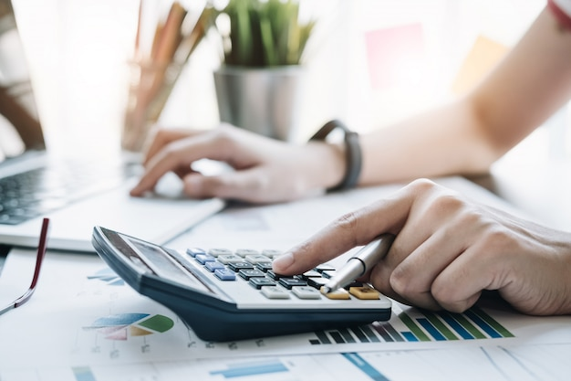 Close up business woman using calculator and laptop for do math finance on wooden desk in office and business working Premium Photo
