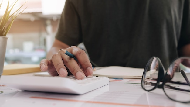 Close up of businessman or accountant hand holding pen working on calculator to calculate business data, accountancy document and laptop computer at office, business concept Premium Photo
