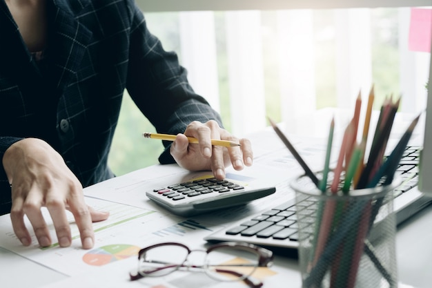 Close up of businessman or accountant hand holding pencil working on calculator Premium Photo