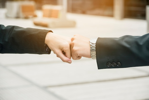 Close-up of businessman and businesswoman making a fist bump Free Photo