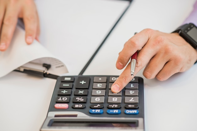 Close-up of businessman calculating invoices using calculator Free Photo