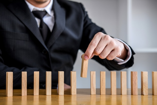 Close up of businessman hand gambling placing wooden block on a line of domino Premium Photo