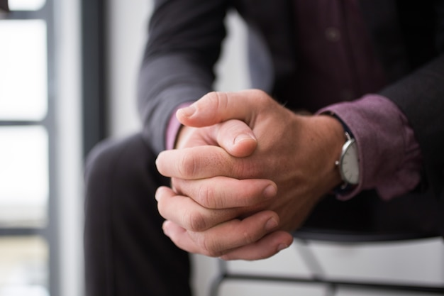 Close-up of businessman hands sitting on chair Free Photo