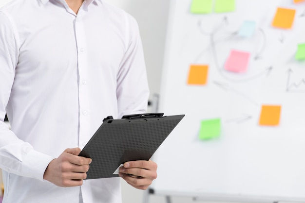 Close-up of a businessman holding black clipboard in hand standing near the flipchart Free Photo
