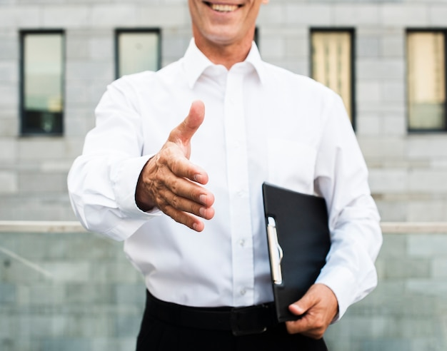 Close-up businessman holding out hand Free Photo