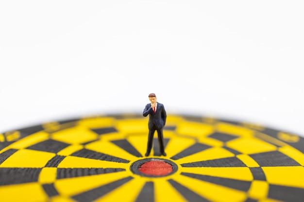 Close up of businessman miniature figure standing close to center of  dart board Premium Photo