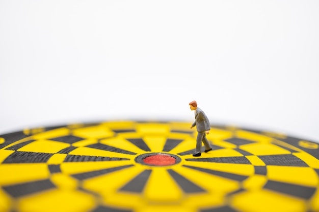 Close up of businessman miniature figure walking to center of  dart board with white. Premium Photo