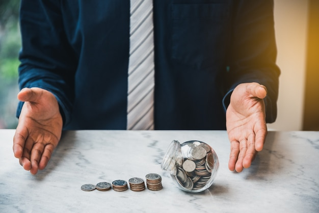 Close up businessman open hand money coin stack with coin in glass on the table. saving money concept, finance accounting concept Premium Photo