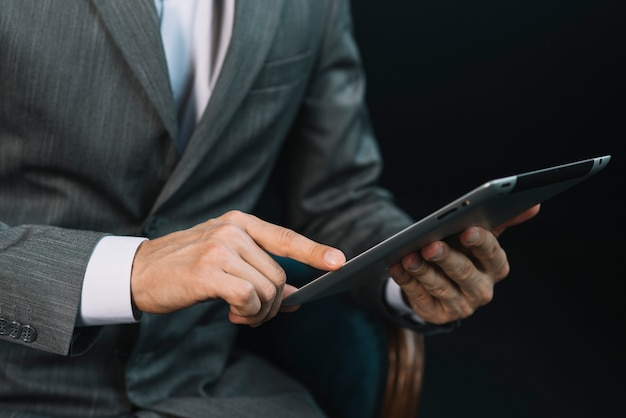 Close-up of a businessman's hand touching the digital tablet screen Free Photo