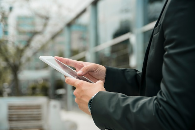 Close-up of businessman's hand using the mobile phone at outdoors Free Photo