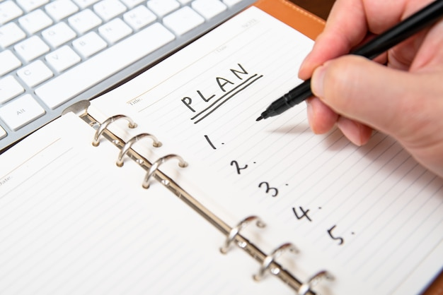 Close-up of a businessman's hand writing plan and list in the diary. Premium Photo