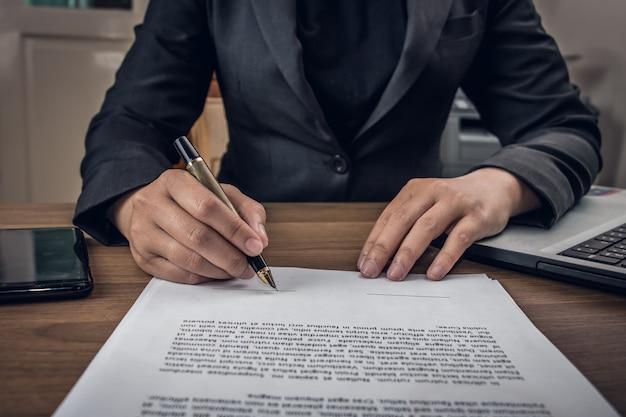 Закройте бизнесмен подписания условий и договора документ на своем столе в офисе Premium Фотографии