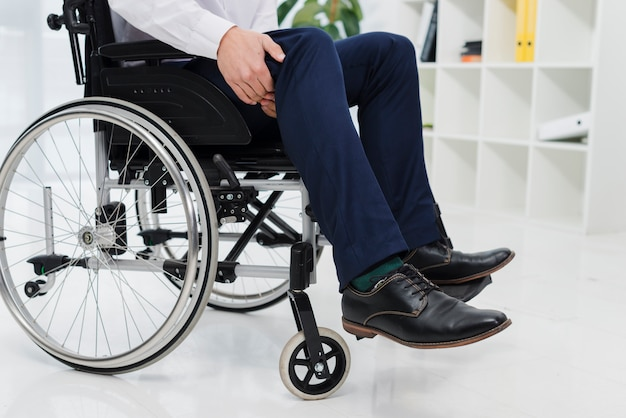 Close-up of a businessman sitting on wheelchair suffering from the leg pain Free Photo
