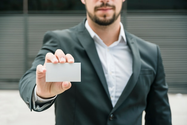 Close-up of a businessman standing at outdoors showing blank white business card Free Photo