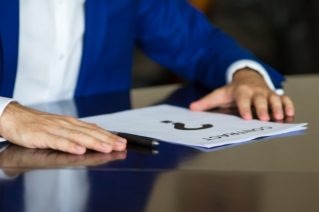 Close up of businessman thinking on a contract paper Premium Photo
