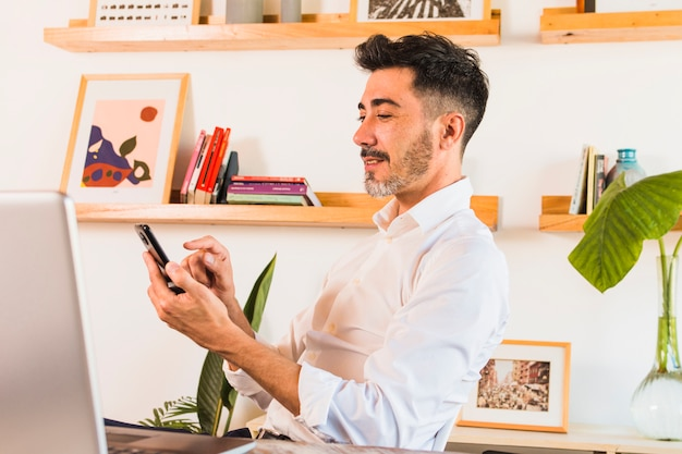 Close-up of businessman using mobile phone in the office Free Photo