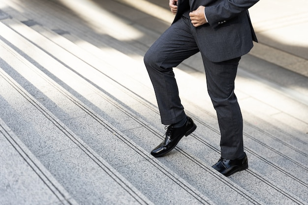 Close up businessman walking stepping up on business district urban, business concept Free Photo
