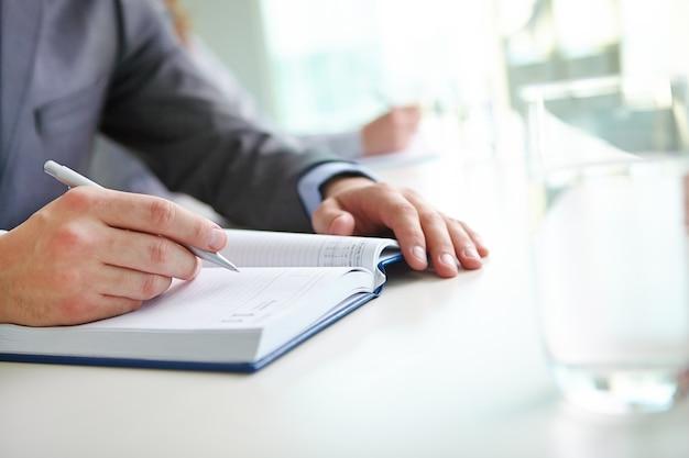 Close-up of businessman writing an idea Free Photo