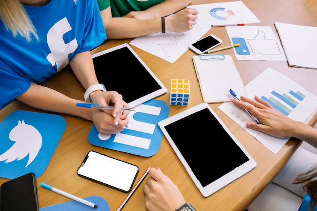 Close-up of businesspeople with digital tablet and social media icons on table Free Photo