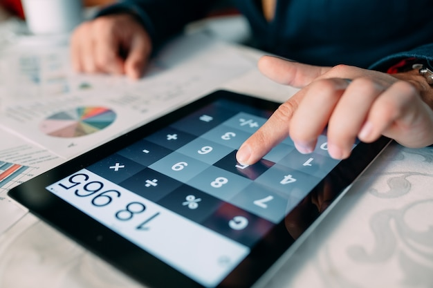 Close-up of a businessperson's hand analyzing bill on digital tablet over desk, Premium Photo