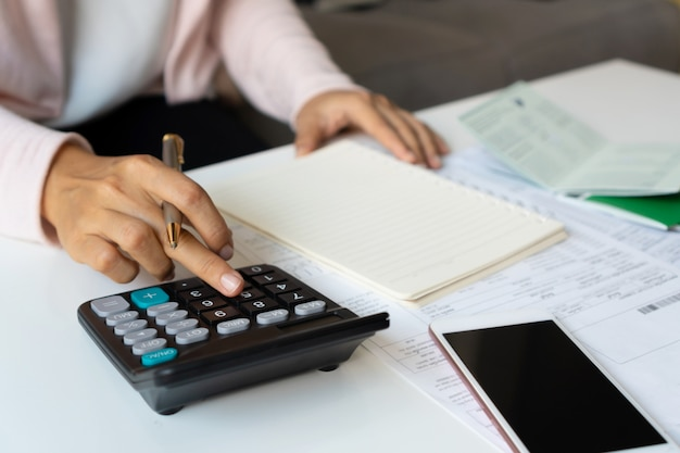 Close up of businesswoman calculating monthy expense at her desk. home saving concept. financial and installment payment concept. Premium Photo
