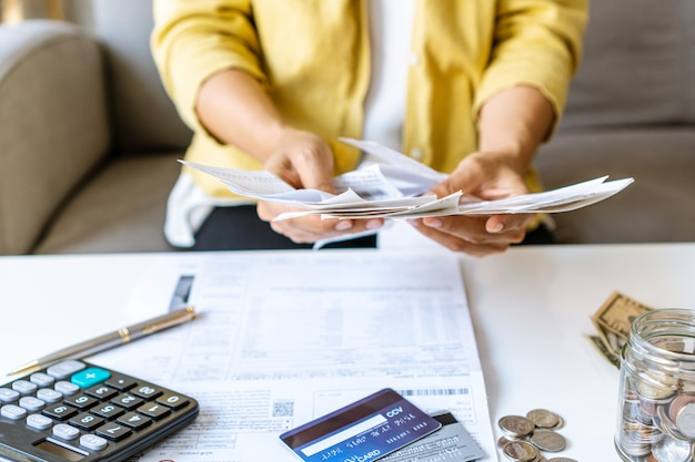Close up of businesswoman checking bills and calculating monthy expense at her desk. home saving concept. financial and installment payment concept. Premium Photo