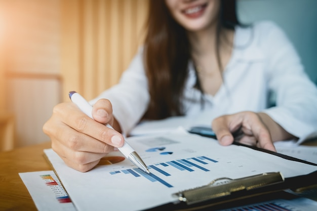 Close up businesswoman hand holding pen and pointing at financial paperwork. Premium Photo