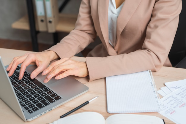 Close-up of businesswoman's hand typing on laptop with pen; diary and spiral notepad on wooden table Free Photo