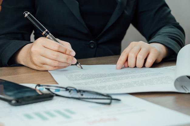 Крупным планом бизнесмен подписания условий и соглашения документ на ее столе Premium Фотографии