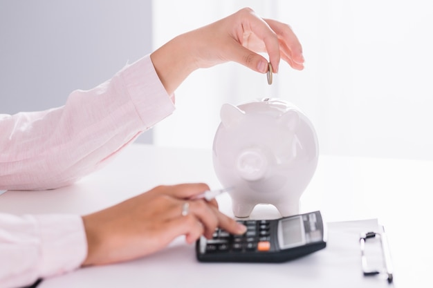 Close-up of businesswoman using calculator inserting coin in piggybank Free Photo
