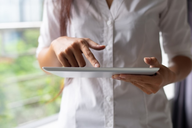 Close-up of businesswoman in white shirt using modern device Free Photo