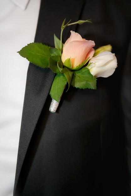 Close up a buttonhole of the groom from beige roses Premium Photo