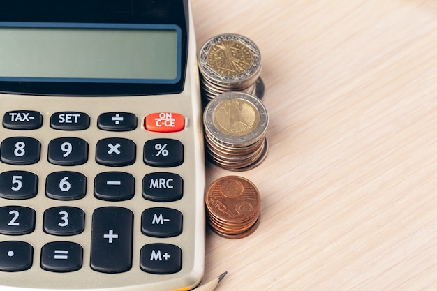 Close up of a calculator and coins on a business Premium Photo